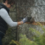 woman paints wall in garden