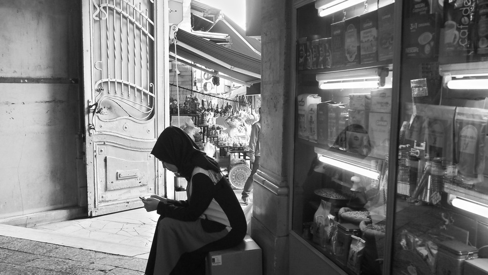 woman in headscarf checks phone in grand bazaar Istanbul