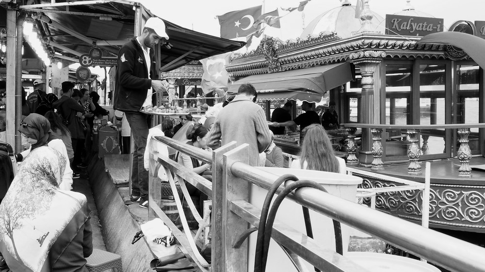 Man sells sweets alongside the famous fishboats on the Eminönü side of the Galata Bridge