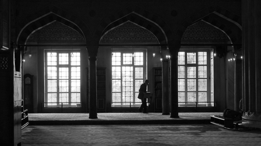 a man moves furniture inside the blue mosque in Istanbul