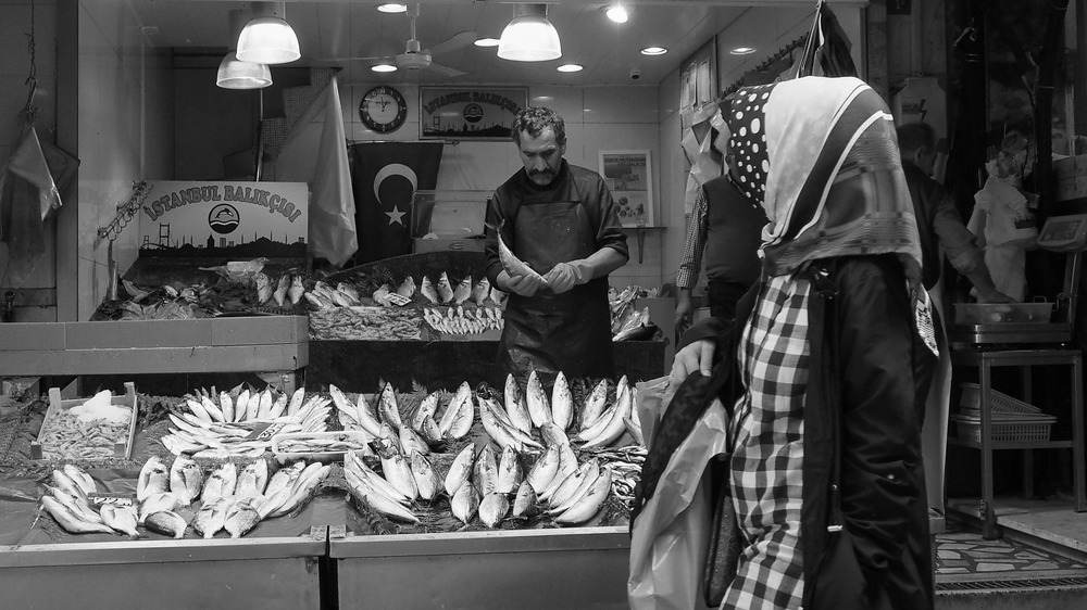women wearing headscarves pass a fish stall in kadikoy market on the Asian side of Istanbul