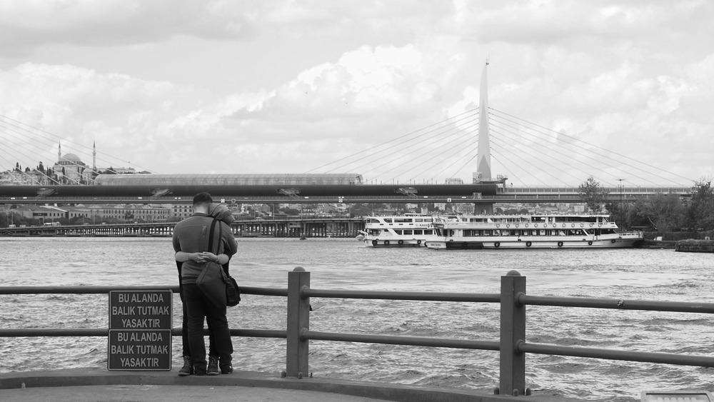 couple embraces on the galata bridge over the Golden Horn