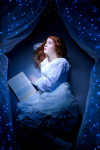 red headed girl with book stargazes under fairy light night sky curtains