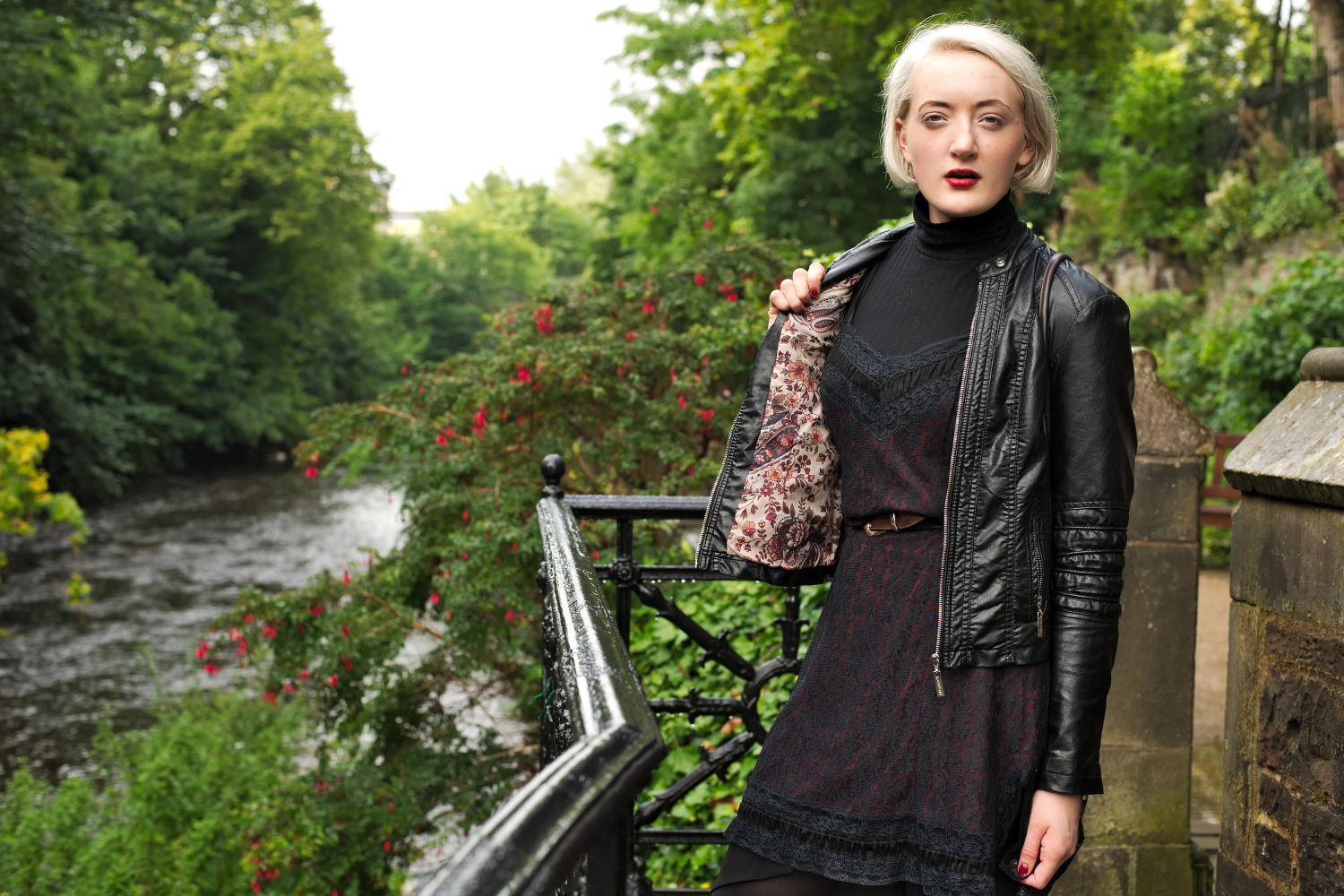 woman models leather jacket along water of leith