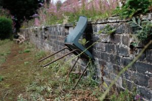blue chair leaning against brick wall community garden edinburgh scotland