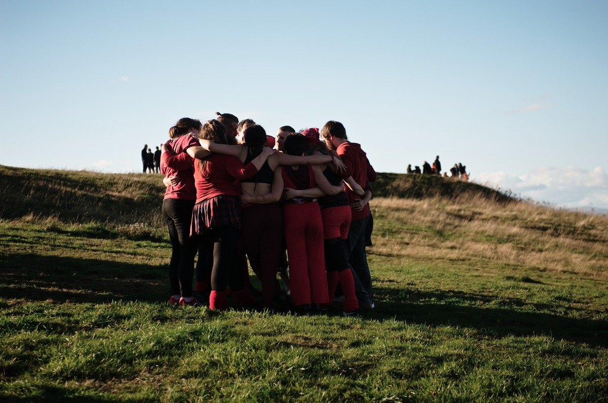 Samhain performers in red huddle together on Calton Hill in Edinburgh
