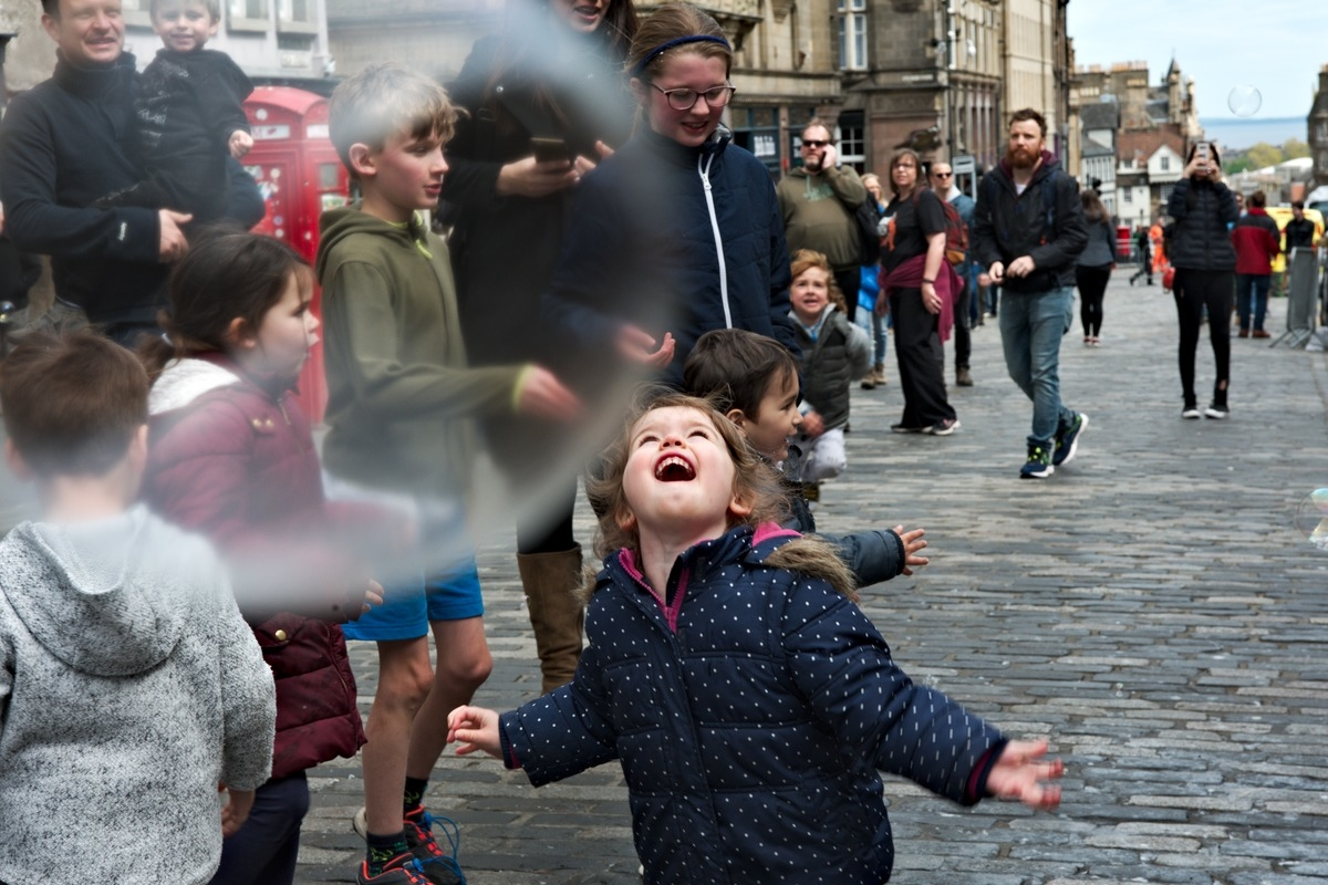 girl enchanted with bubbles on royal mile Edinburgh Scotland