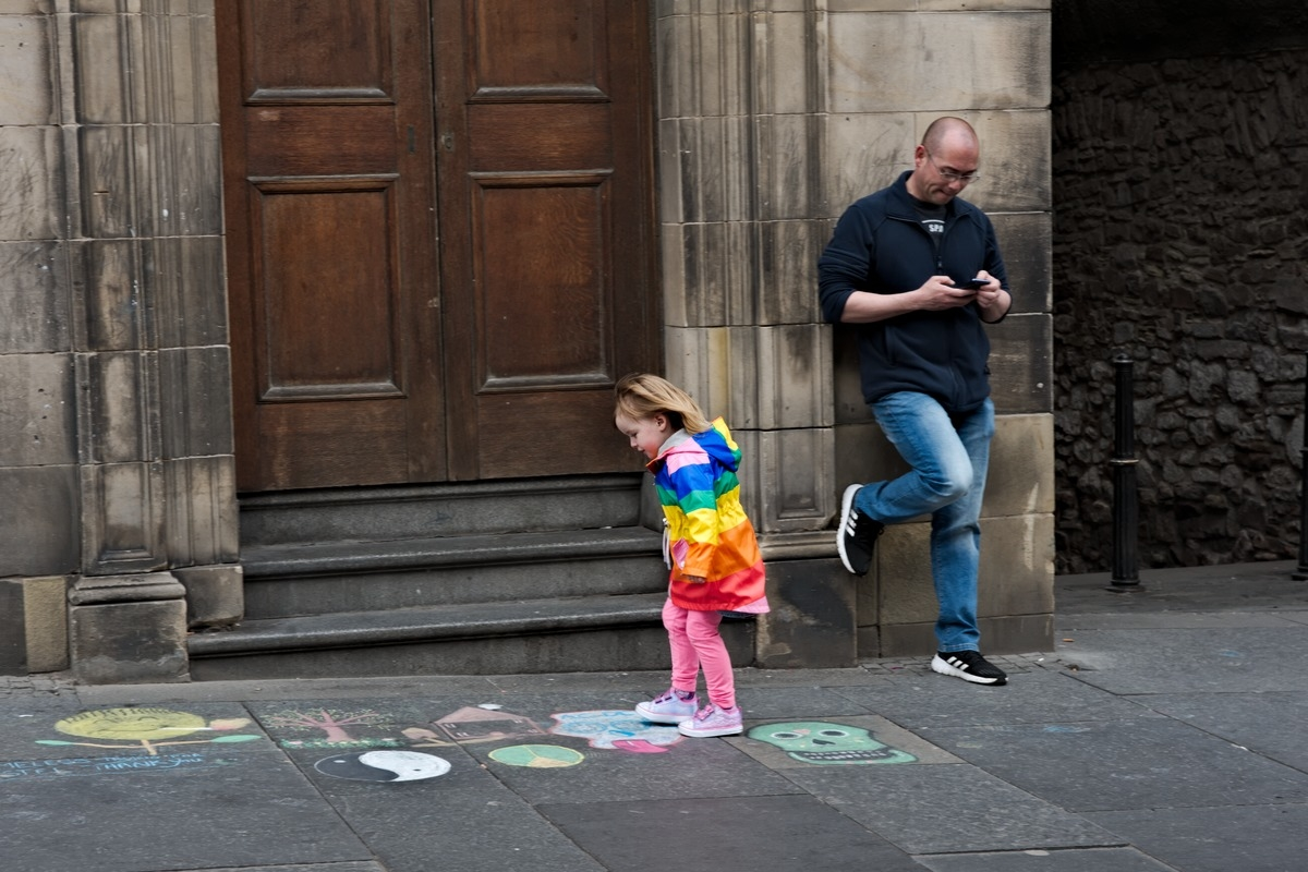 girl in rainbow jacket hopscotches chalk drawings pavement