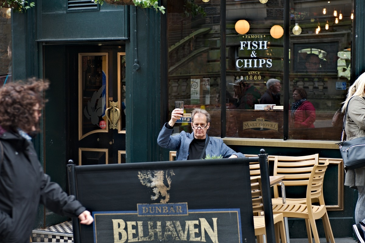 man raises pint glass sitting outside pub in Edinburgh Scotland