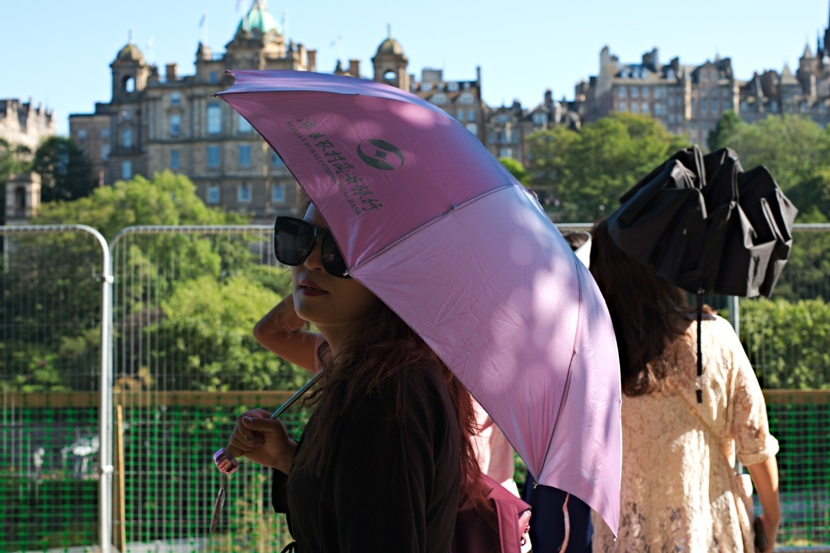 woman with sunglasses and pink umbrella in Edinburgh Scotland
