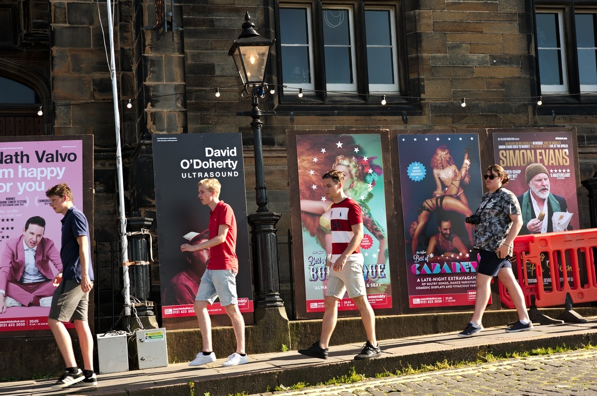 family walks in front of Edinburgh Fringe Festival posters